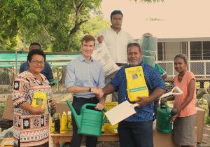 A handshake between High Commissioner Jones and Minister Filualea with the donated seeds and tools.